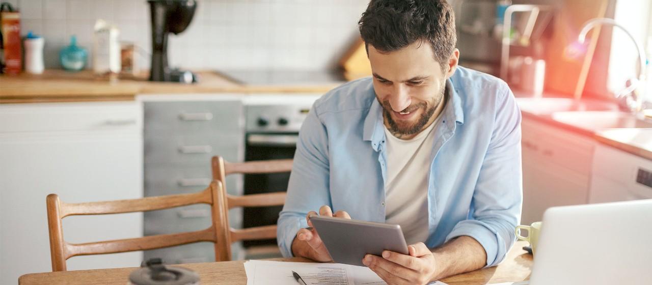 Mann mit Tablet in Wohnung